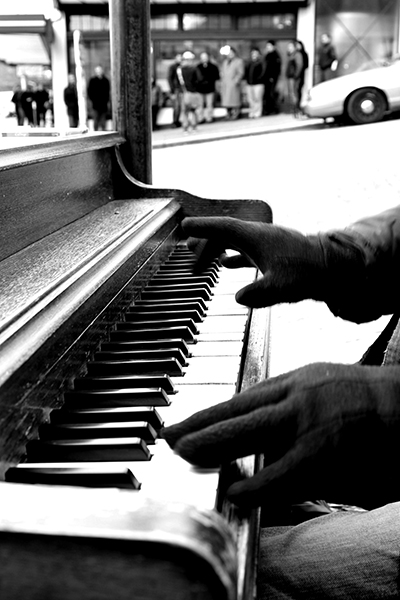 Gloved hands playing an outdoor piano