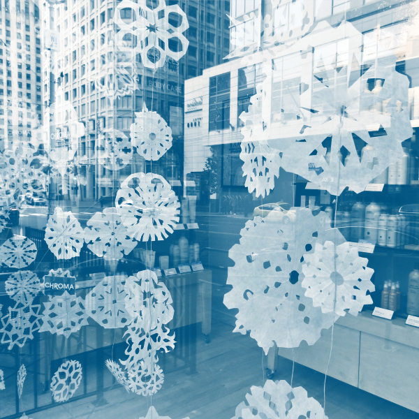 paper snowflake garland through a window storefront